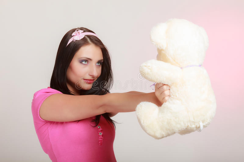 Childish woman infantile girl hugging teddy bear. Portrait of childish young woman with headband holding toy. Infantile girl hugging teddy bear on pink. Longing royalty free stock photos