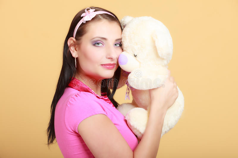 Childish woman infantile girl hugging teddy bear. Portrait of childish young woman with headband holding toy. Infantile girl in pink hugging teddy bear on orange royalty free stock photo