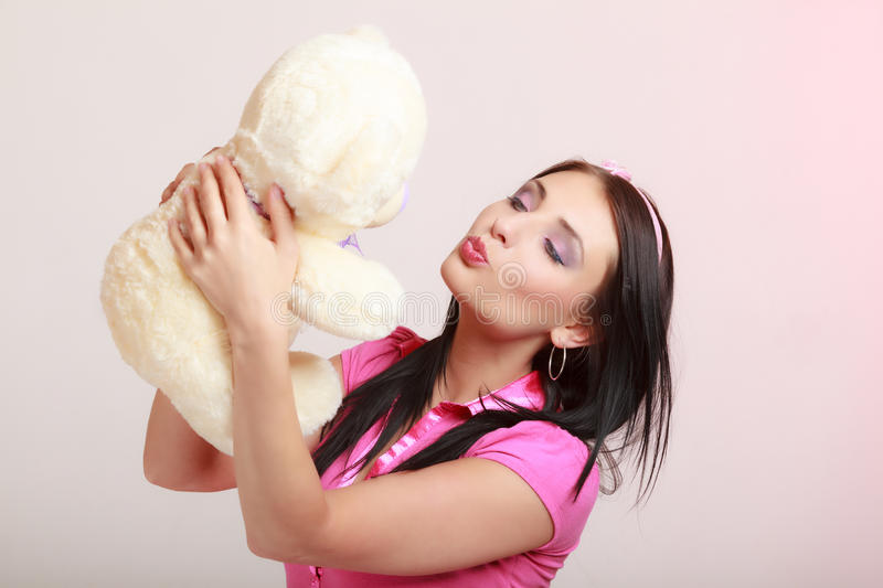 Childish woman infantile girl kissing teddy bear. Portrait of childish young woman with headband holding toy. Infantile girl hugging kissing teddy bear on pink royalty free stock photo