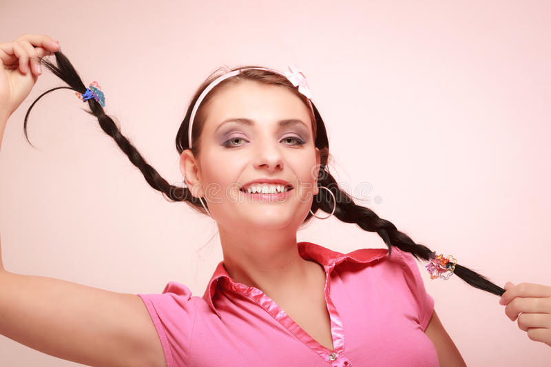 Childish woman infantile girl with pigtail. Longing for childhood. Portrait of childish young woman with pigtail. Infantile girl in headband doing fun on pink stock images