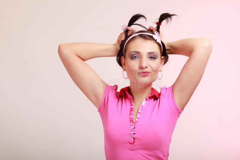 Childish woman infantile girl with pigtail. Longing for childhood. Portrait of childish young woman with pigtail. Infantile girl in headband doing fun on pink stock photos