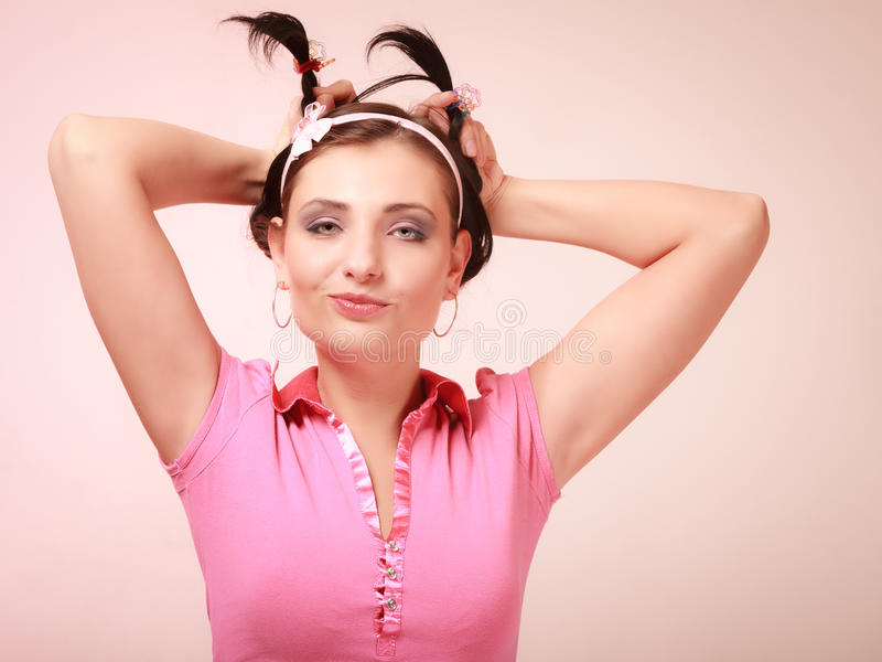 Childish woman infantile girl with pigtail. Longing for childhood. Portrait of childish young woman with pigtail. Infantile girl in headband doing fun on pink stock photography