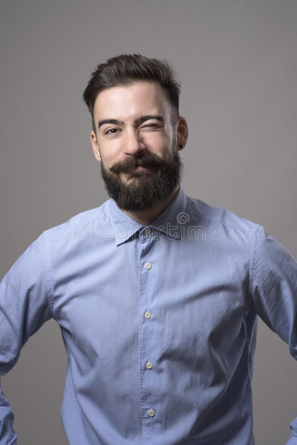 Childish young bearded hipster in formal wear winking with funny expression looking at camera royalty free stock photography