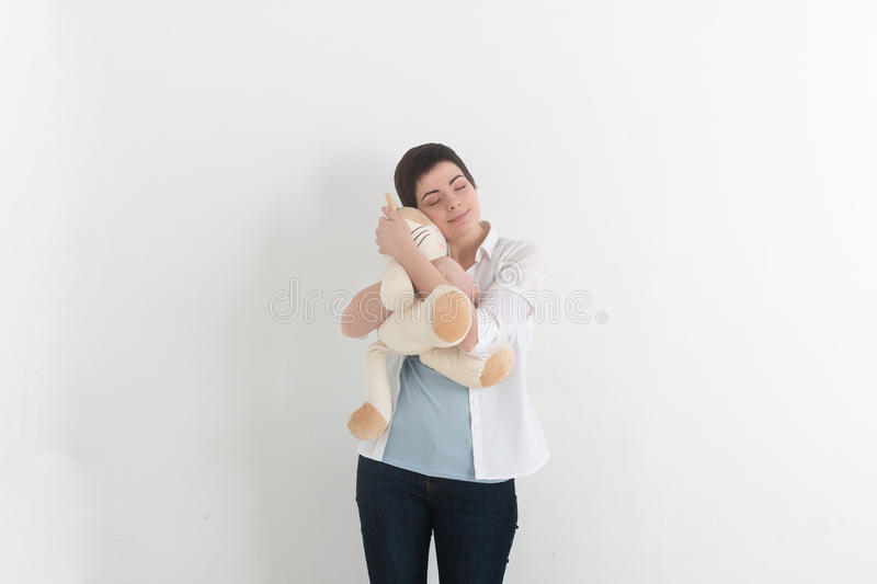 Childish young woman hugging soft plush cat with innocent smile and closed eyes. Sweet dreams. royalty free stock photo