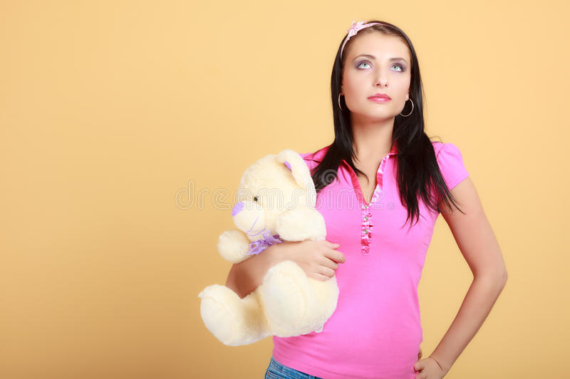 Childish young woman infantile girl in pink hugging teddy bear toy royalty free stock photos