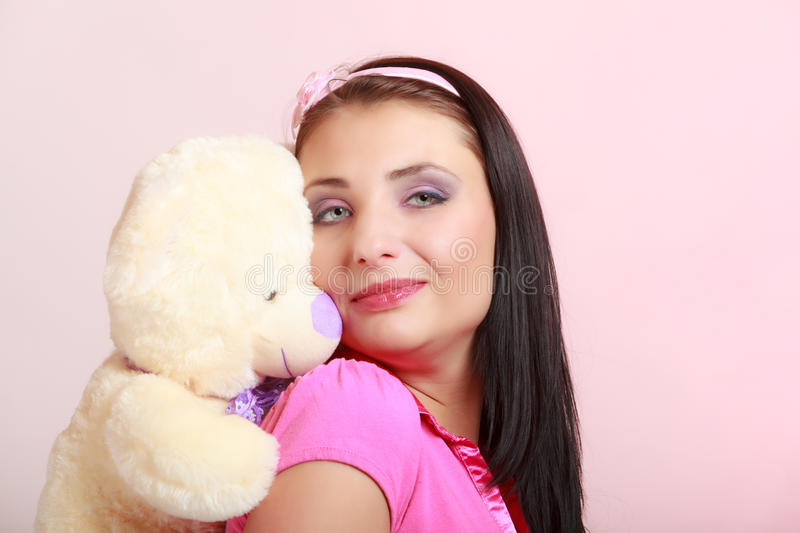 Childish young woman infantile girl in pink hugging teddy bear toy. Portrait of childish young woman with headband holding toy. Infantile girl hugging teddy bear royalty free stock photo