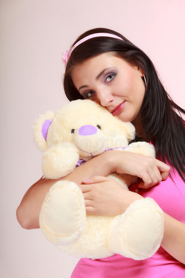 Childish young woman infantile girl in pink hugging teddy bear toy. Portrait of childish young woman with headband holding toy. Infantile girl hugging teddy bear stock photos