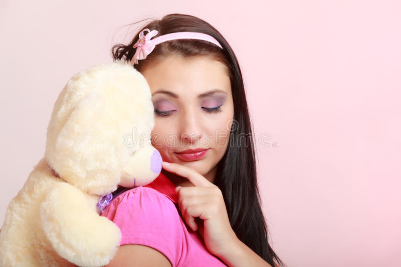 Childish young woman infantile girl in pink hugging teddy bear toy. Portrait of childish young woman with headband holding toy. Infantile girl hugging teddy bear stock photography