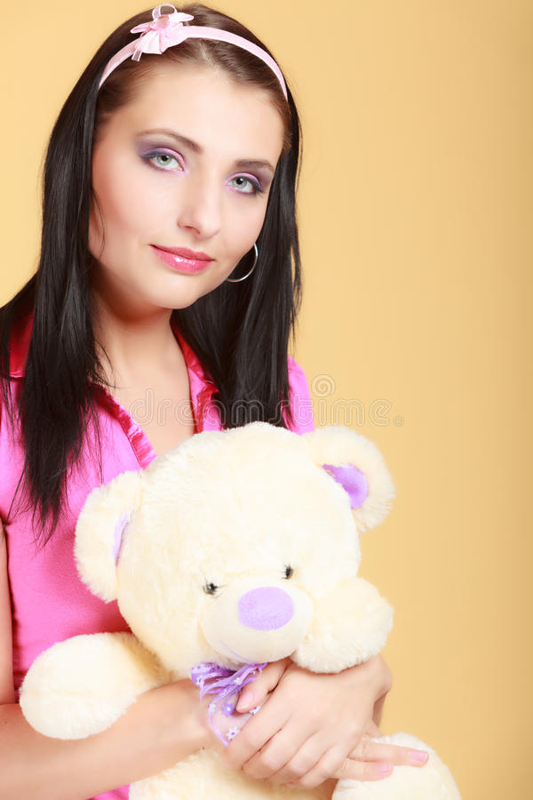 Childish young woman infantile girl in pink hugging teddy bear toy. Portrait of childish young woman with headband holding toy. Infantile girl in pink hugging royalty free stock images