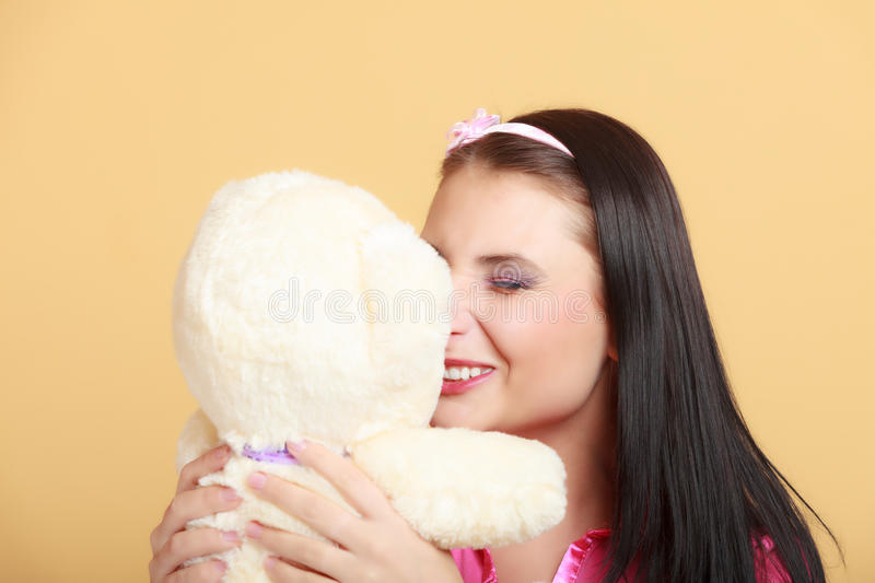 Childish young woman infantile girl in pink hugging teddy bear toy. Portrait of childish young woman with headband holding toy. Infantile girl in pink hugging royalty free stock image