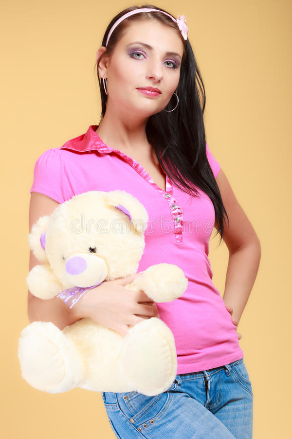 Childish young woman infantile girl in pink hugging teddy bear toy. Portrait of childish young woman with headband holding toy. Infantile girl in pink hugging royalty free stock photo
