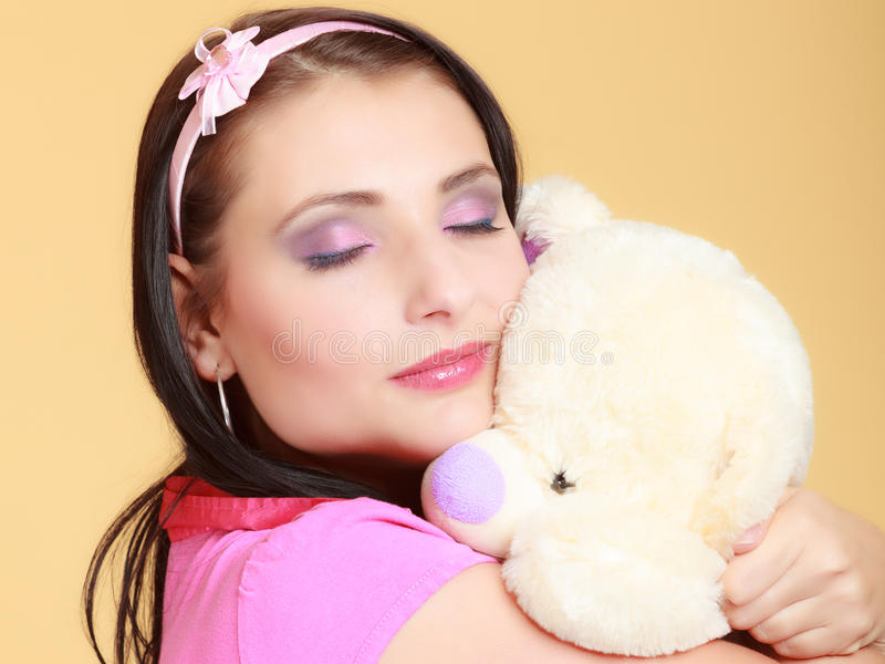 Childish young woman infantile girl in pink hugging teddy bear toy. Portrait of childish young woman with headband holding toy. Infantile girl in pink hugging stock photo