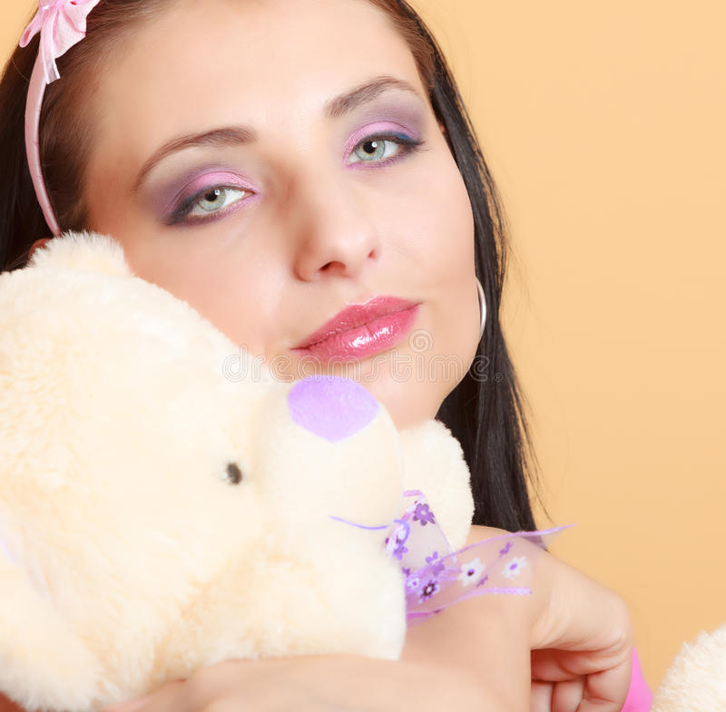 Childish young woman infantile girl in pink hugging teddy bear toy. Portrait of childish young woman with headband holding toy. Infantile girl in pink hugging stock photos