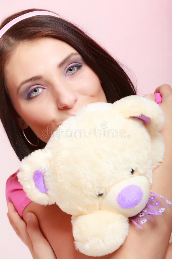 Childish young woman infantile girl in pink kissing teddy bear toy. Portrait of childish young woman with headband holding toy. Infantile girl hugging kissing royalty free stock photos