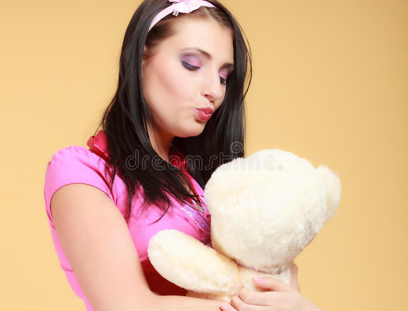 Childish young woman infantile girl in pink kissing teddy bear toy. Portrait of childish young woman with headband holding toy. Infantile girl in pink hugging royalty free stock image