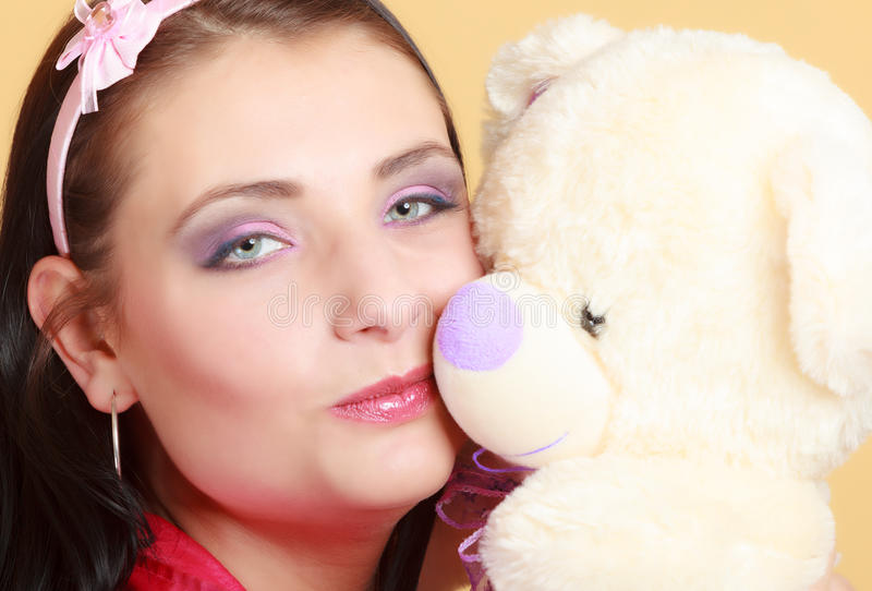 Childish young woman infantile girl in pink kissing teddy bear toy. Portrait of childish young woman with headband holding toy. Infantile girl in pink hugging stock image