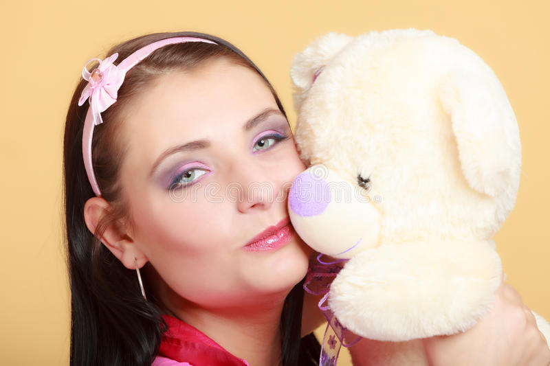 Childish young woman infantile girl in pink kissing teddy bear toy. Portrait of childish young woman with headband holding toy. Infantile girl in pink hugging stock photography