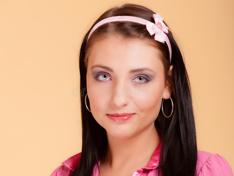 Childish young woman infantile girl in pink. Longing for childhood. Portrait of childish young woman with headband on her hair. Infantile girl in pink on orange royalty free stock photography