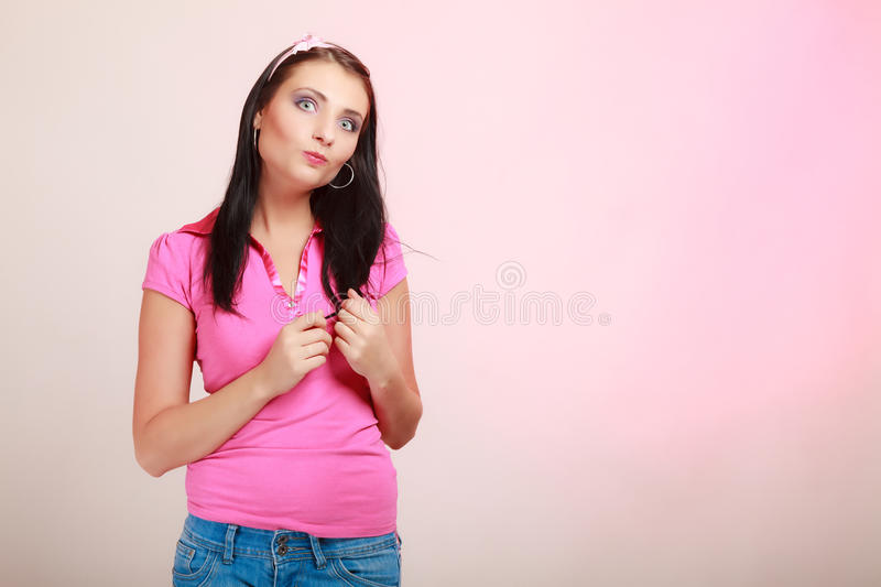 Childish young woman infantile girl in pink. Longing for childhood. Portrait of childish young woman with headband on her hair. Infantile girl making funny stock images