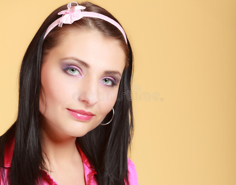 Childish young woman infantile girl in pink. Longing for childhood. Portrait of childish young woman with headband on her hair. Infantile girl in pink on orange stock photo