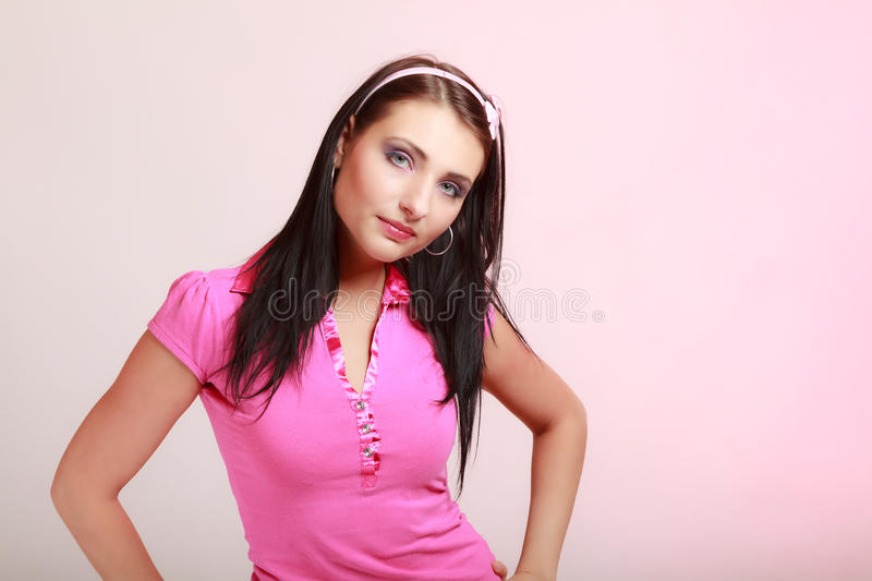 Childish young woman infantile girl in pink. Longing for childhood. Portrait of childish young woman with headband on her hair. Infantile girl on pink. Longing stock photography