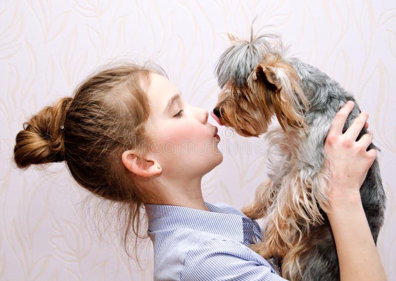 Childl sonriente adorable de la niña que se sostiene y que juega con el terrier de Yorkshire del perrito fotografía de archivo