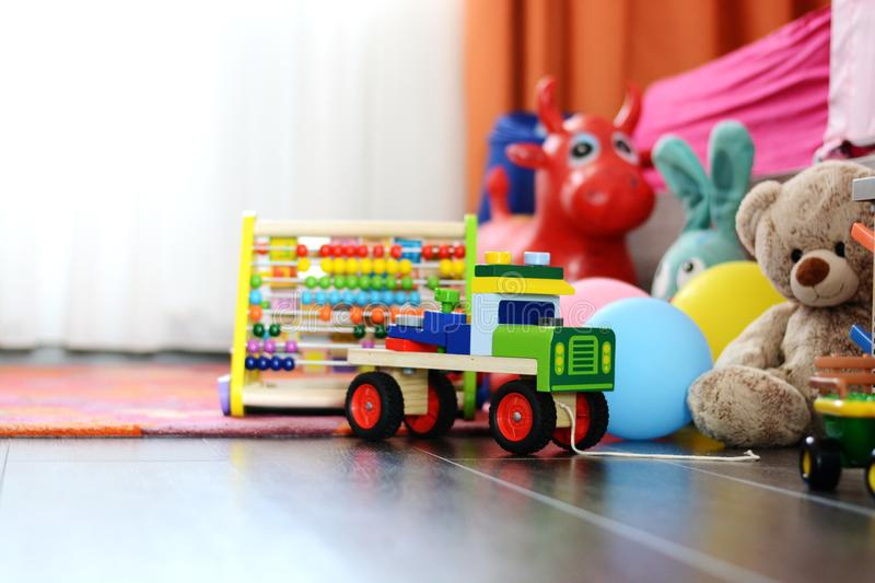Children's multicolored toys on wooden floor or carpet on kids room stock photo