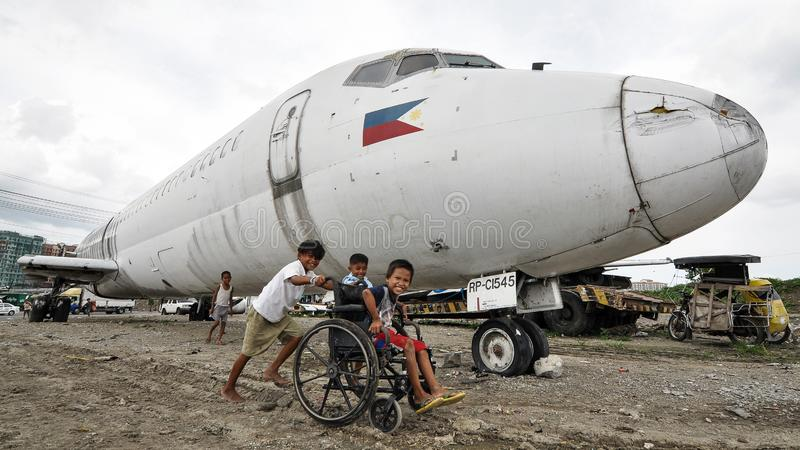 Children's Playground. Children play near a wrecked airplane abandoned in a dumpsite in Paranaque City, south of Manila, Philippines stock image