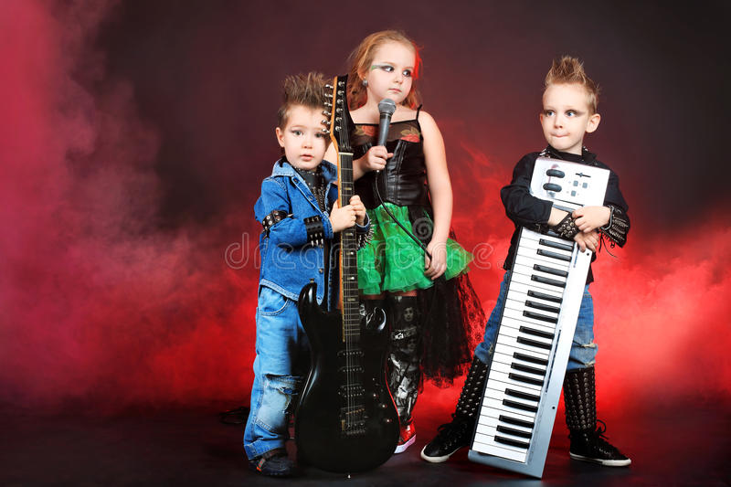 Children. Heavy metal musician with children Shot in a studio royalty free stock photography