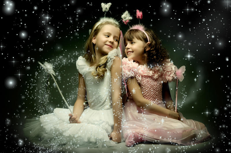 Children. Two beautiful little girl with wings, sit and smile on dark starry sky background stock image