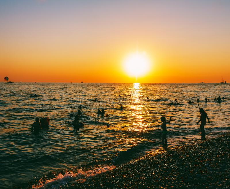 Children and adults swim in the sea in the evening royalty free stock photos