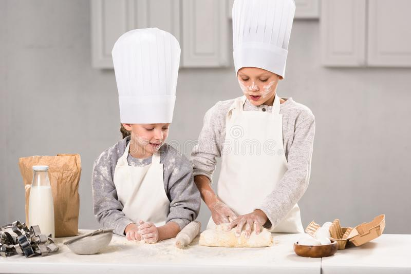 Children in aprons and chef hats making dough with rolling pin at table. In kitchen stock photo
