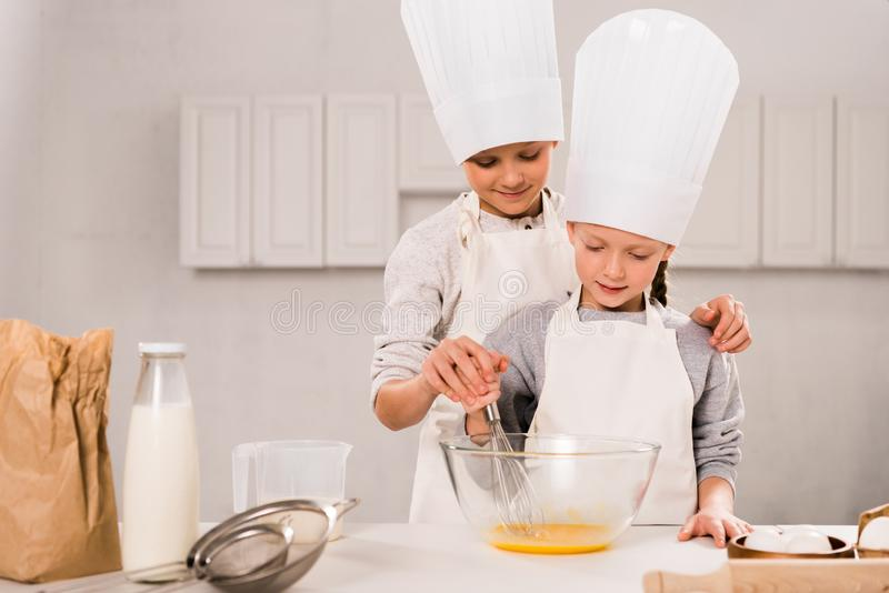 Children in aprons and chef hats whisking eggs in bowl at table. In kitchen royalty free stock photo