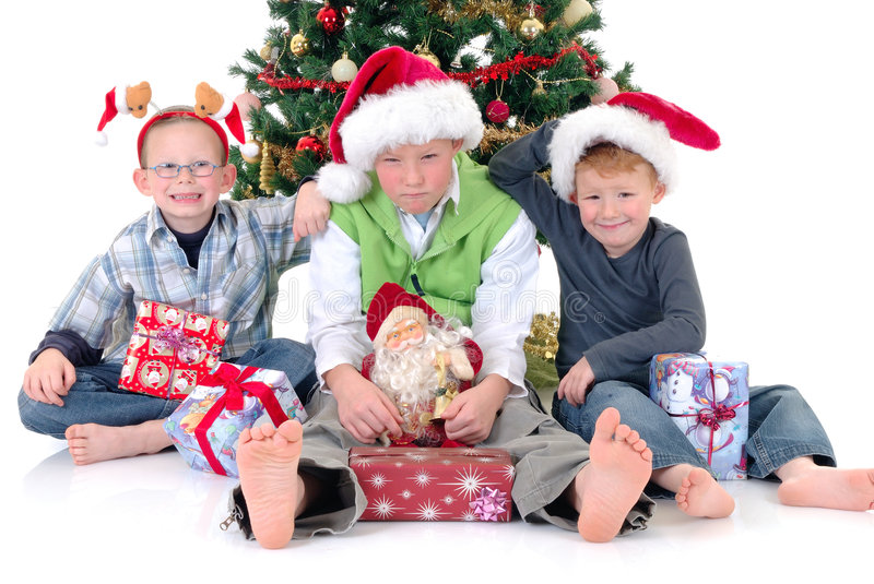 Children around Xmas three. Happy youngsters, three boys in front of Xmas, Christmas three with presents, gifts. White background royalty free stock image