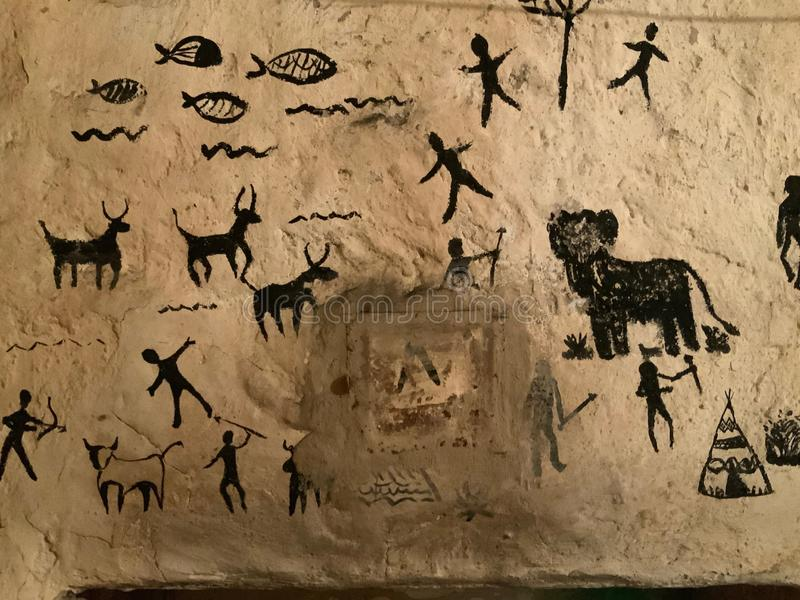 Children art in cave paintings on the stone wall. Prehistoric hunt painted in black stock photos
