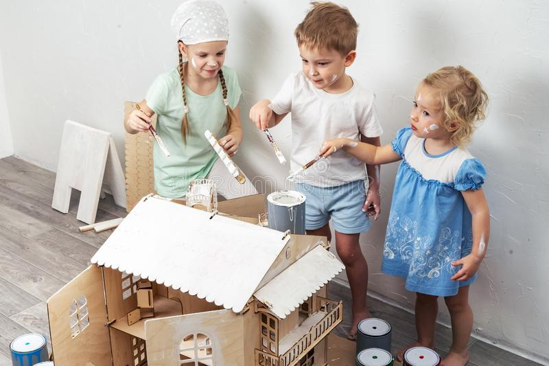Children as adults: A boy and a girl paint a doll house white and get dirty with paint. Authentic photo. stock photo