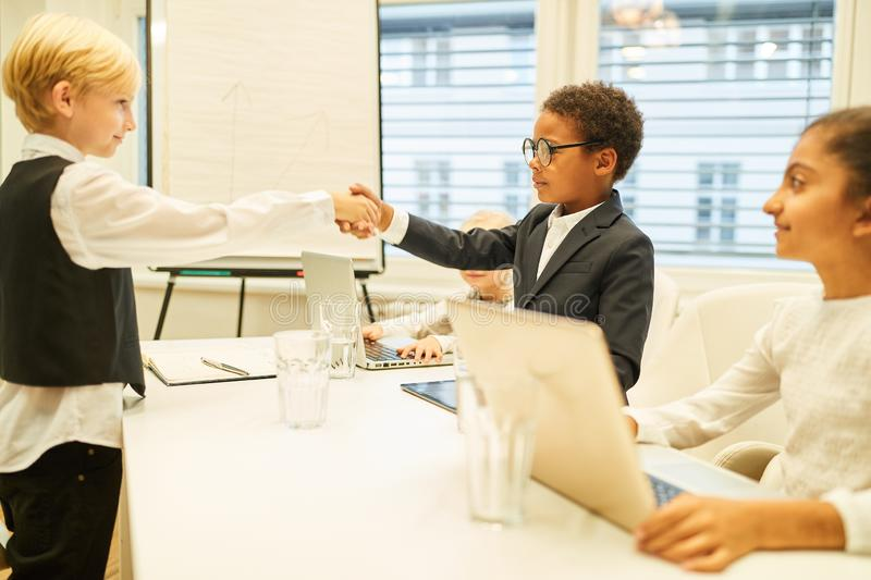 Children as business people greet each other with a handshake. In the conference room royalty free stock image