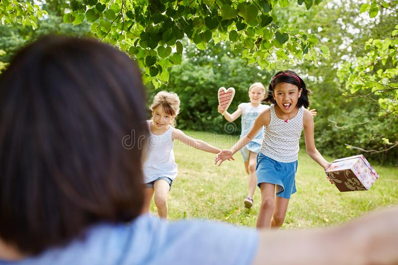 Children as friends run with birthday presents. Children as friends run with joy with birthday presents to party royalty free stock photo
