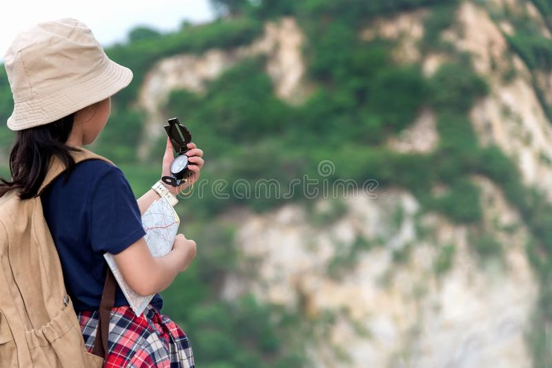 Children asian girl holding maps and Magnetic compass travel backpacks standing in the mountain stock image
