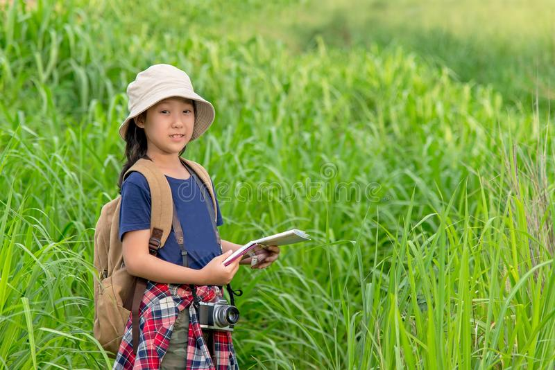 Children asian girl holding maps and travel backpacks walking in the green forest. stock photo