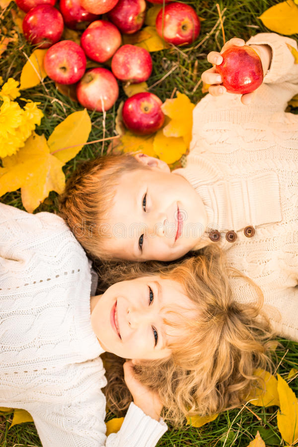 Children in autumn park. Happy children lying on fall leaves. Funny kids outdoors in autumn park royalty free stock photo