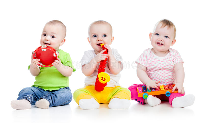 Children babies play musical toys. Children playing with musical toys on white background royalty free stock image
