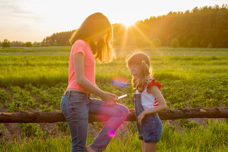 Hildren in the background of nature play with a smartphone. royalty free stock photo