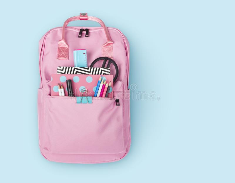 Children backpack with various school stationery isolated on blue background stock photo
