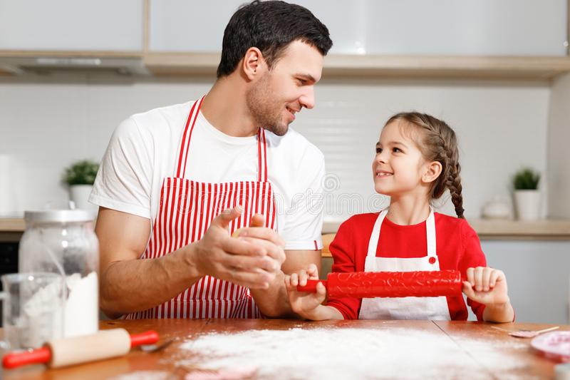 Children, baking, family concept. Cheerful brunet male wears apron and kneads dough, happy girl holds rolling pin, ready royalty free stock photography