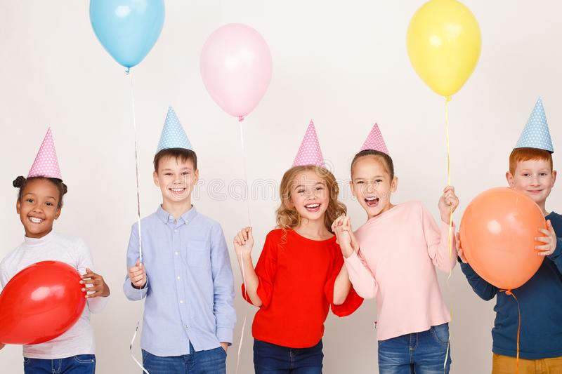Children with balloons having fun at birthday party. Over light background stock images