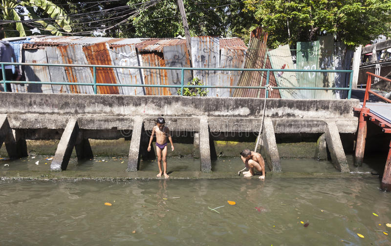 Children in Bangkok. Children living near Khlong chanel in Bangkok swim in its dirty water. CAPTION Young boy jumps in polluted water of Khlong chanel royalty free stock images
