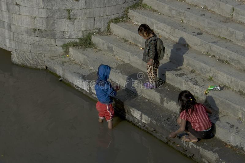 Children on the bank of the sacred river near the cremation site stock image