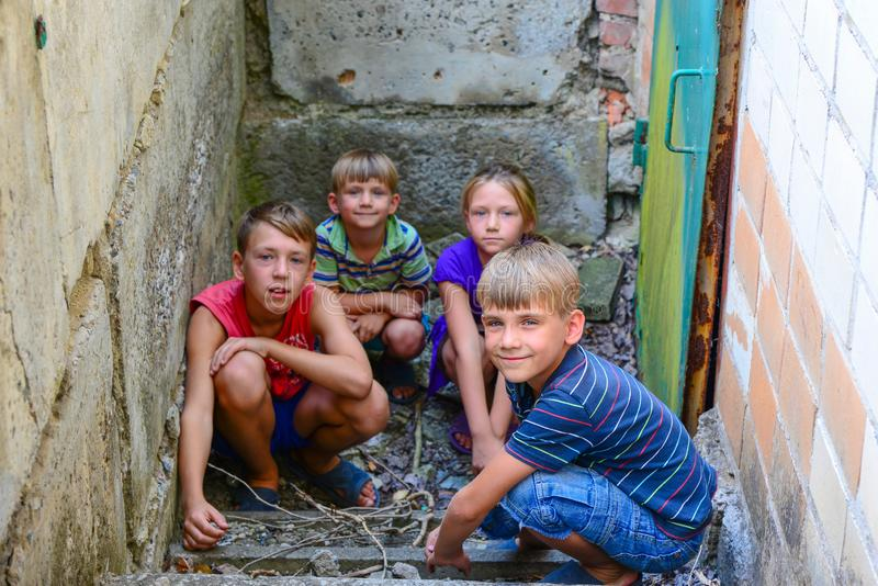 Children in the basement, three boys and a girl near the iron door are hiding on the steps from the outside world. Post-production. Photo stock photography