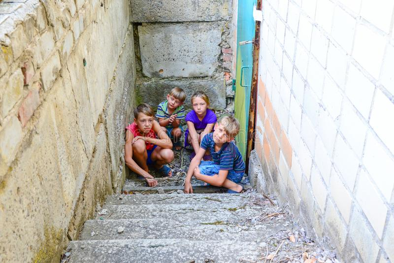 Children in the basement, three boys and a girl near the iron door are hiding on the steps from the outside world. Post-production. Photo royalty free stock photos